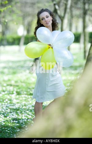 Giovane donna camminare in prato, tenendo palloncini, guardando lontano Foto Stock
