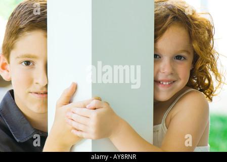 Fratello e Sorella di peeking attorno alla colonna in telecamera, tenendo le mani, sorridente Foto Stock