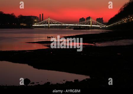 Albert Bridge poco dopo il tramonto, fire-red sky visto dalla riva del Tamigi, Chelsea Embankment, London, England, Foto Stock