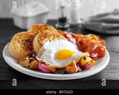 La completa prima colazione inglese con cialdine, servita su una piastra bianca in una tabella - uova fritte, pancetta, Foto Stock