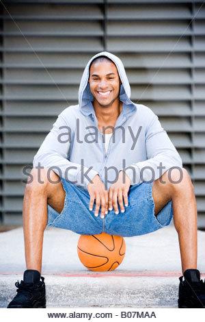 Ritratto di un giovane sorridente African American uomo in grigio di un top con cappuccio seduti su un pallone da Foto Stock