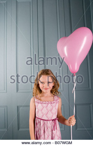 Bambina in party dress holding rosa a forma di cuore palloncino Foto Stock
