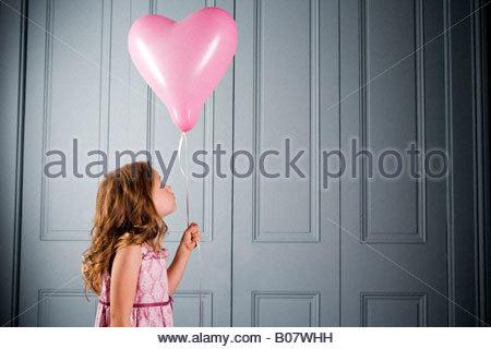 Bambina in party dress guardando il suo cuore rosa a forma di palloncino Foto Stock