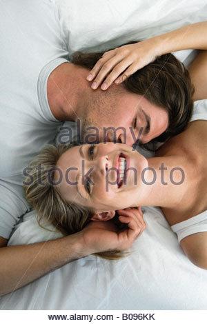 Coppia giovane giacente in letto, sorridente, baciare, ritratto da sopra Foto Stock