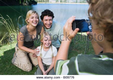 Ragazzo fotografare la famiglia all'aperto, padre, madre e sorella che posano per una foto Foto Stock