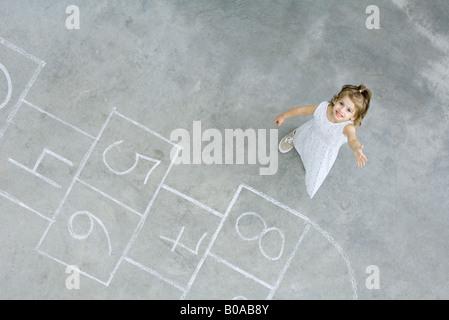 Bambina in piedi accanto a campana piazze, sorridente fino alla fotocamera, ad alto angolo di visione Foto Stock
