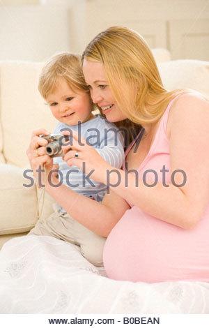 Donna incinta che mostra la fotocamera al bimbo figlio 15-18 mesi, dal divano Foto Stock