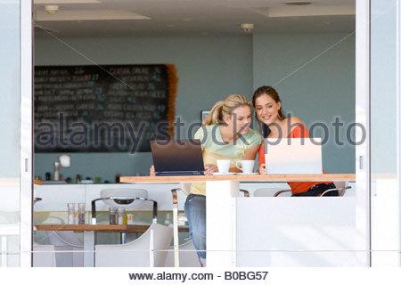 Due ragazze adolescenti seduto con i laptop in cafe, sorridente Foto Stock