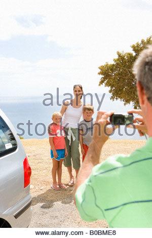 Padre tenendo fotografia della madre con il figlio e la figlia (6-10) sulla spiaggia, sorridente Foto Stock
