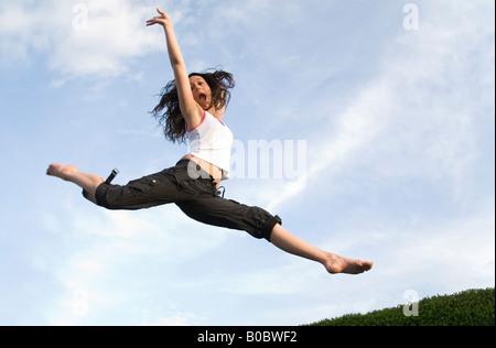 Una ragazza adolescente saltando su un trampolino