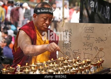 'No i diritti umani' afferma il segno su una fascia di monaci tra i manifestanti che si sono riuniti in Janpath, Foto Stock