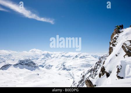 Gli appassionati di snowboard che guarda oltre le montagne nevose Foto Stock