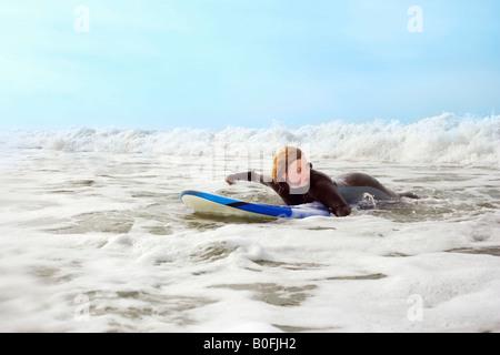 Femmina giacente sulla tavola da surf, canoa Foto Stock