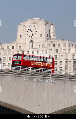 Londra Inghilterra un bus rosso a due piani passa sopra il ponte di Waterloo con Shell Mex House dietro Foto Stock