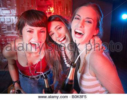 Tre donne in un night club di bere e ridere Foto Stock