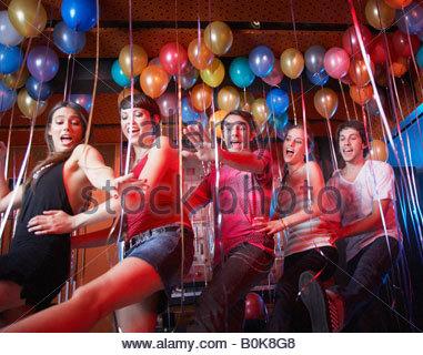 Cinque persone in una discoteca dancing e sorridente Foto Stock