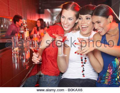 Tre donne con bevande in discoteca di puntamento e sorridente Foto Stock