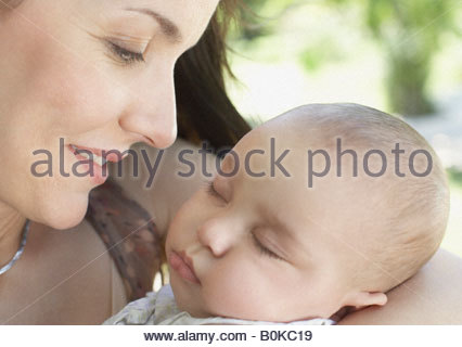 Donna all'aperto azienda sleeping baby e sorridente Foto Stock