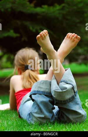 Giovane ragazza rilassante con un libro su erba verde in un parco di estate