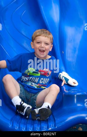 3 anno vecchio ragazzo gioca sul parco giochi in un parco in Tampa Florida Foto Stock