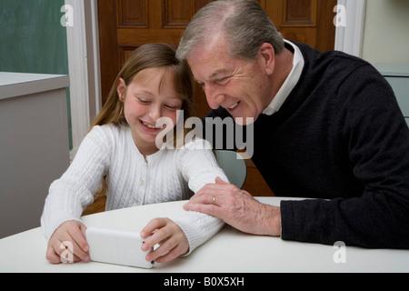 Un nipote utilizzando un dispositivo elettronico durante il suo nonno watch Foto Stock