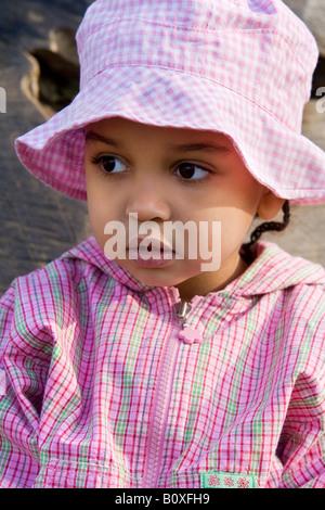 Un bel po' di razza mista ragazza abiti in rosa plaid patterns Foto Stock