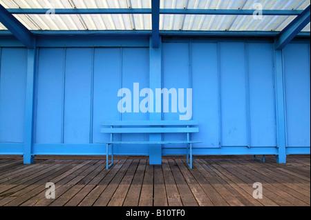 Un vuoto azzurro panca su un molo vecchio Foto Stock