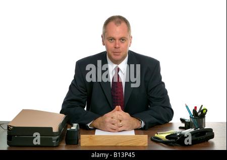 Ritratto di un imprenditore seduto alla sua scrivania contro uno sfondo bianco Foto Stock