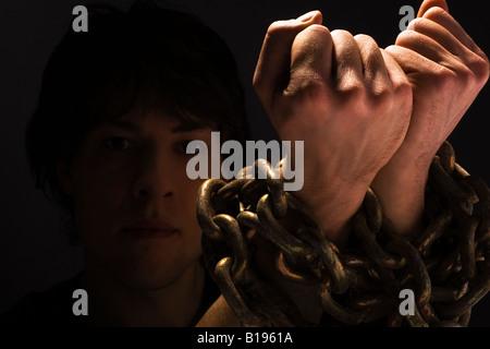 Uomo con le catene sul suo polsi Foto Stock