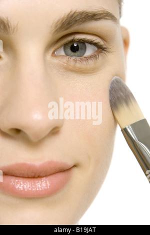 Donna di applicare il make-up a guancia, sorridente in telecamera, close-up Foto Stock