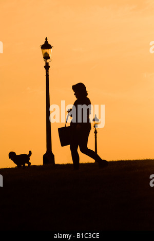 Silhouette di una donna che cammina il suo cane al tramonto di Primrose Hill Londra