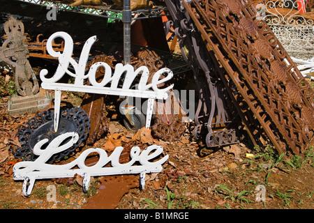 Giardino di metallo decorazioni di parole di amore e di casa accanto a arrugginito oggetti di metallo Foto Stock