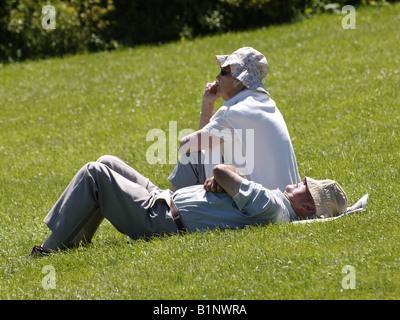 Vecchia coppia sull'erba godendo il sole estivo. Foto Stock