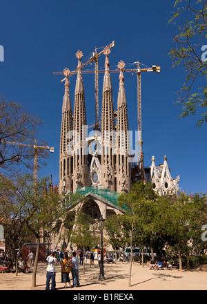 I turisti di fronte la chiesa della Sagrada Familia progettata dall'architetto Antoni Gaudí, vista panoramica fatta di 3 distinti pi