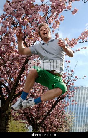 Il 33-anno-vecchio uomo jumping nella città in primavera Foto Stock