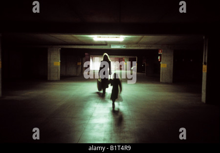 Donna e bambino a piedi nel parcheggio sotterraneo illuminato da una luce fluorescente Foto Stock