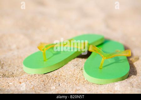 Coppia di green flip flop sulla spiaggia. Foto Stock