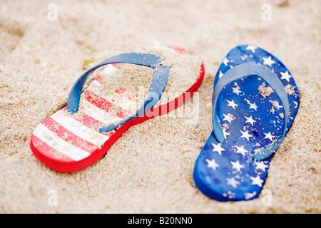 Stelle e strisce flip flop nella sabbia Foto Stock