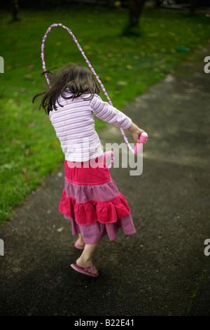 Ragazza di età compresa tra i quattro imparare a saltare nota è un marchio Disney corda Foto Stock