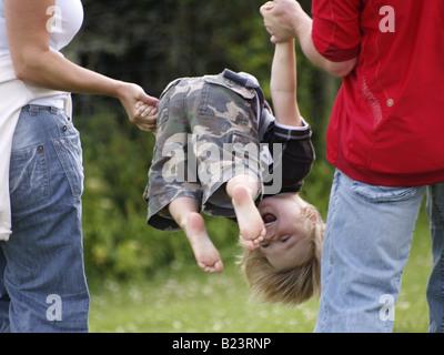 Little Boy essendo filata intorno in aria dai suoi genitori Foto Stock