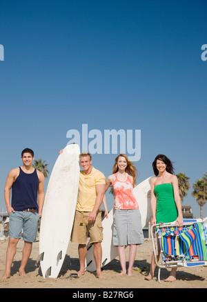 Gruppo di amici in piedi sulla spiaggia Foto Stock