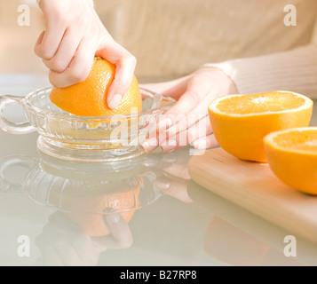 La donna la spremitura di arance Foto Stock