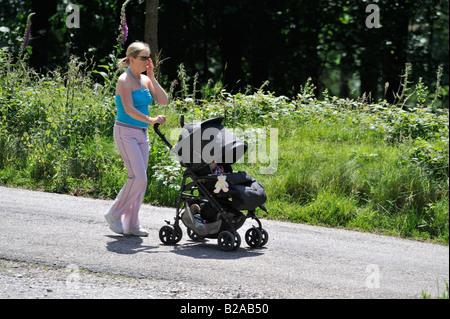 Madre spingendo il bambino nel passeggino fuori per una passeggiata lungo le molte belle e interessanti percorsi Foto Stock