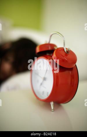 Ragazza di età compresa tra i cinque posti letto nel suo letto accanto a Colore rosso brillante sveglia razza mista Foto Stock