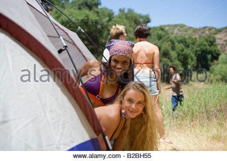 Due donne prendendo le loro teste fuori da una tenda Foto Stock