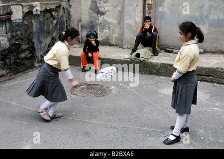 Bambini che giocano gli elastici o il cinese Salto con la corda, Cihangir district, Istanbul, Turchia Foto Stock