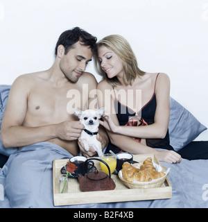 Giovane e bella coppia caucasica in un letto su sfondo isolato avente la colazione a letto Foto Stock