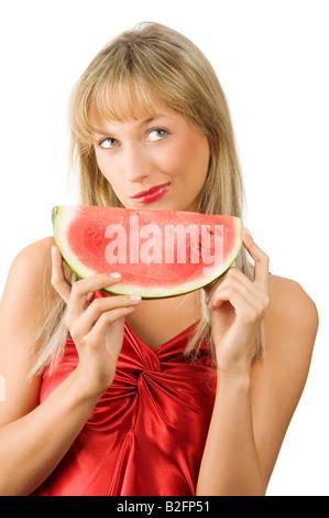 Carina ragazza bionda in abito rosso e rosso le labbra con un pezzo di cocomero rendendo la faccia Foto Stock