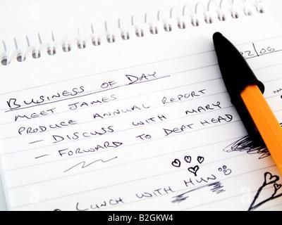 Doodle schizzo foderato di affari di lavoro Notepad con annoiato disegni e arancione nera Biro BIC Marcatore su Foto Stock