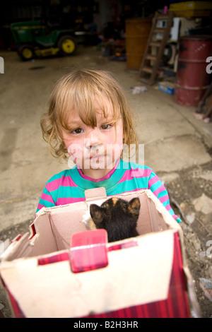 Ragazza giovane nelle zone rurali di Iowa, scatola di contenimento di nuovo i gattini, Iowa, USA Foto Stock